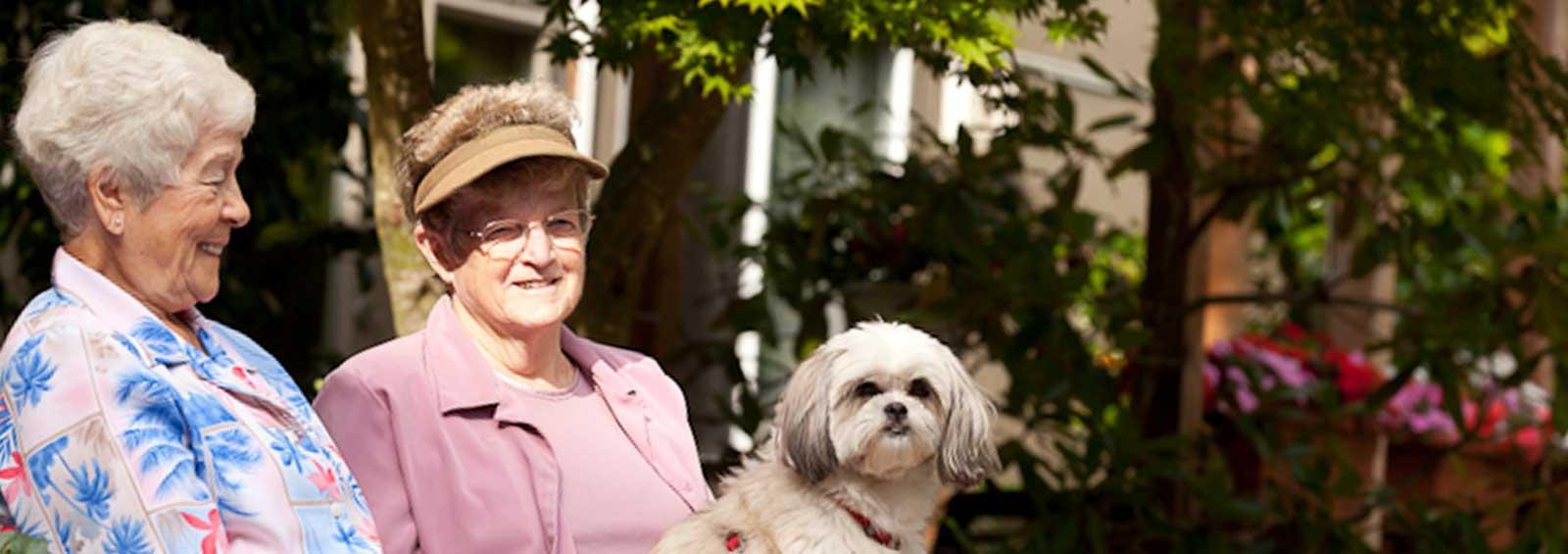 VRS Lakeside Gardens Seniors Community Home smiling senior residents with dog in garden