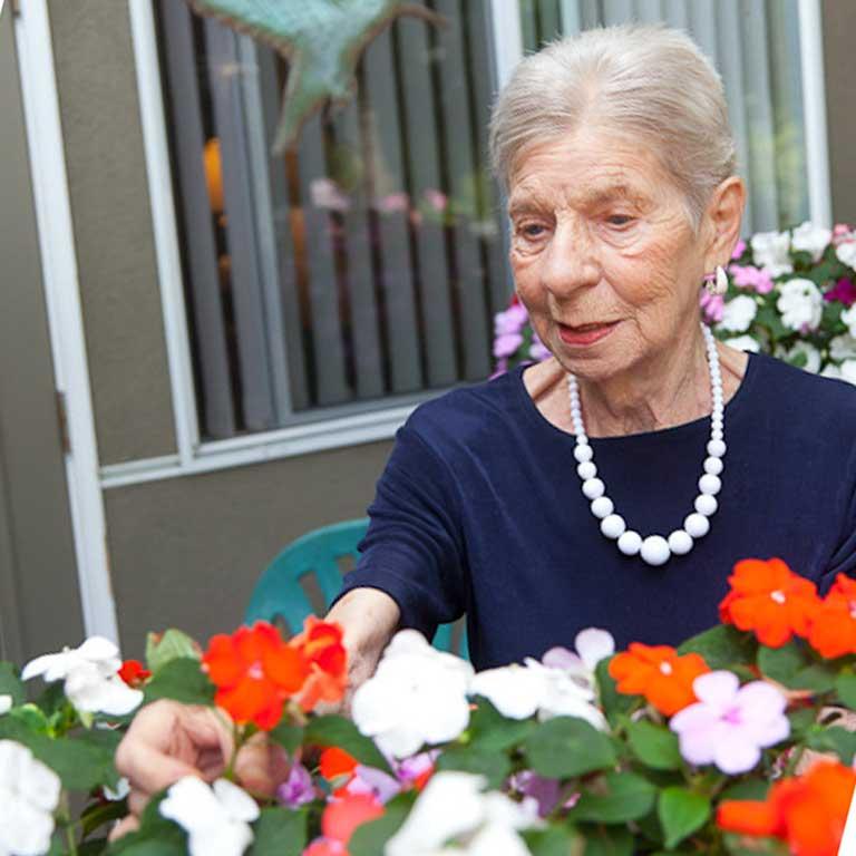 VRS Lakeside Gardens Seniors Community Our Story our mission happy senior resident picking flower in garden