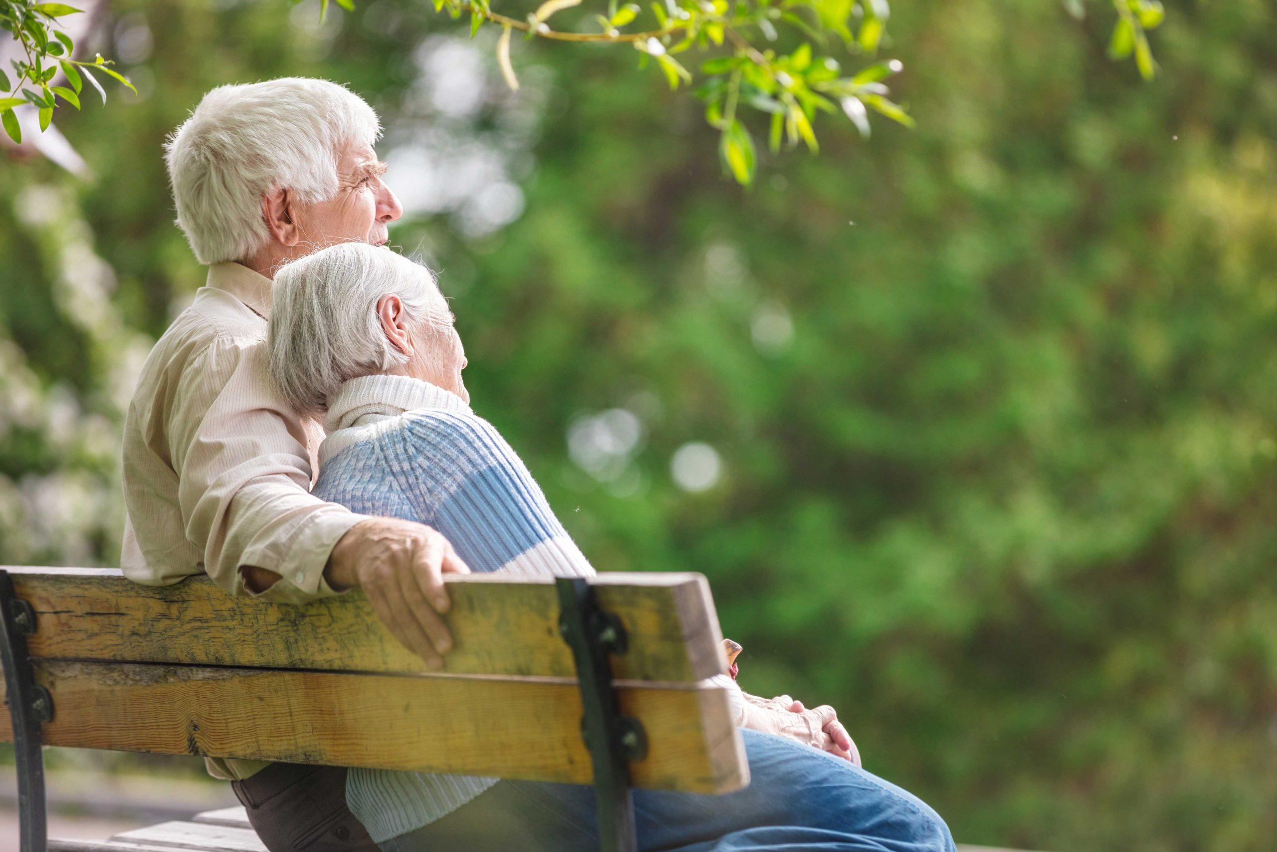 Senior couple sitting together on bench outside
